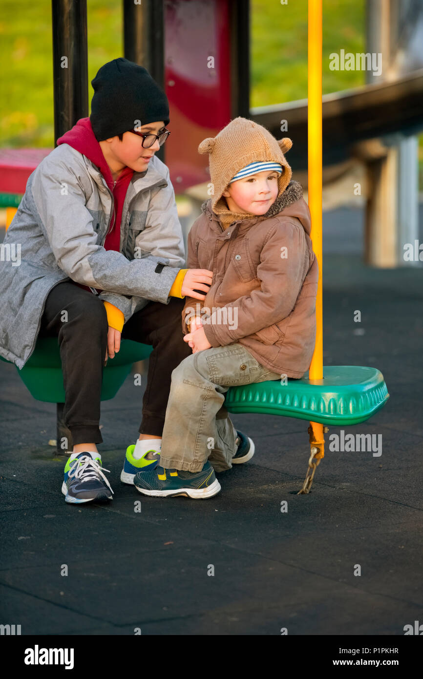A young boy with his older brother sitting and talking at a playground; Langley, British Columbia, Canada - Stock Image
