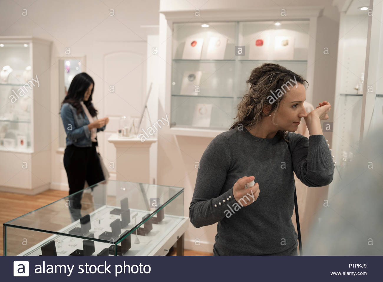 Woman trying on perfume at boutique - Stock Image