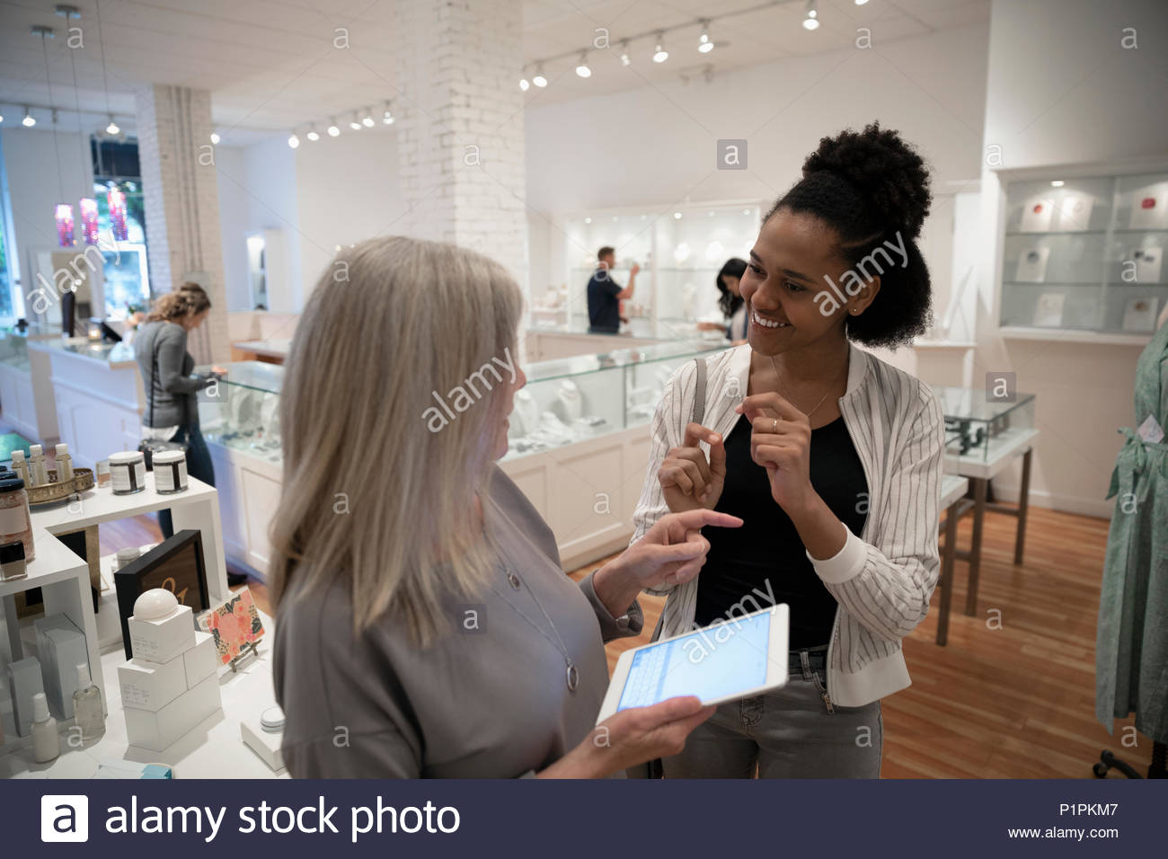 Boutique owner with digital tablet helping woman shopping - Stock Image