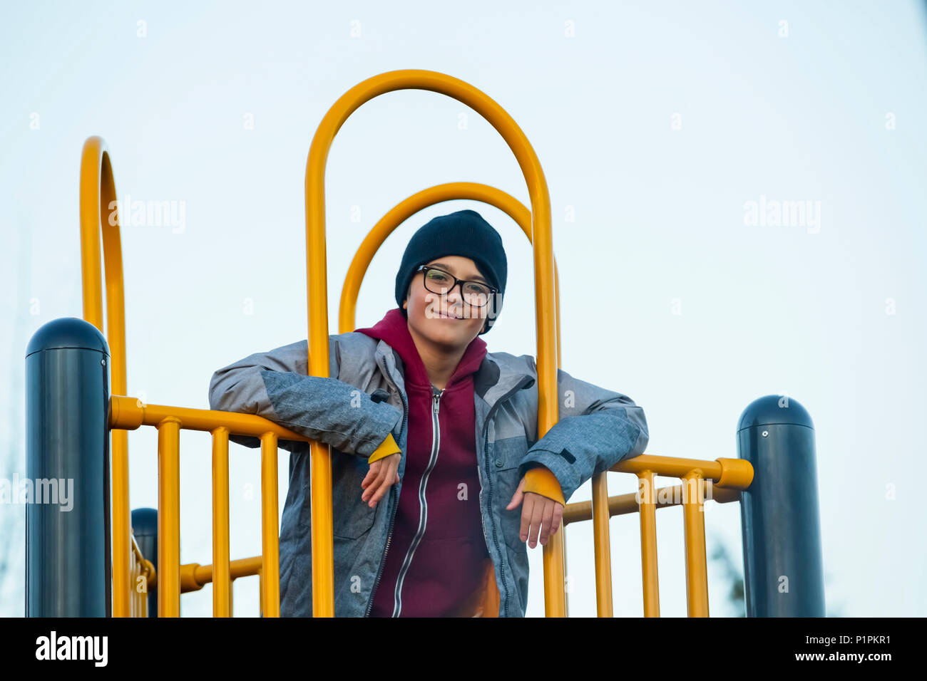 Portrait of a young boy playing on playground equipment; Langley, British Columbia, Canada - Stock Image