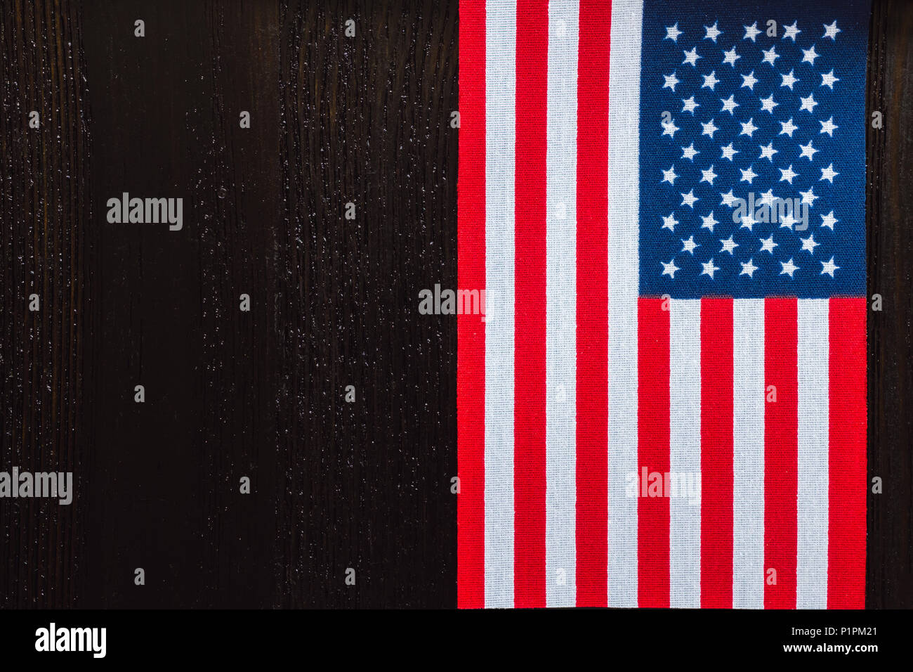 vertical american flag with space for copy on dark wood table stock