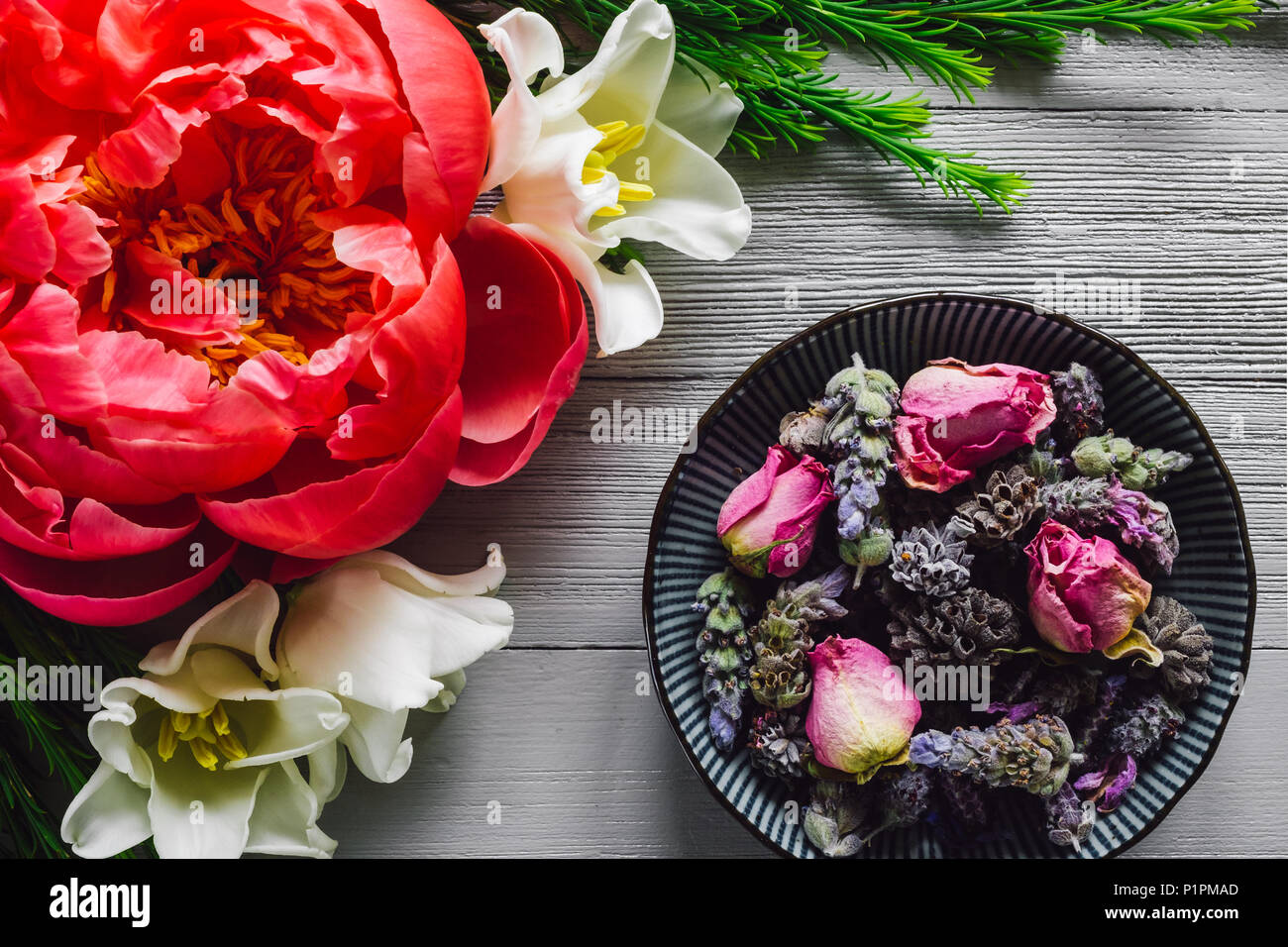 Bowl of Dried Flowers, Including, Lavender, Rose and White Sage,  on White Table with Tulip and Peony Flowers - Stock Image