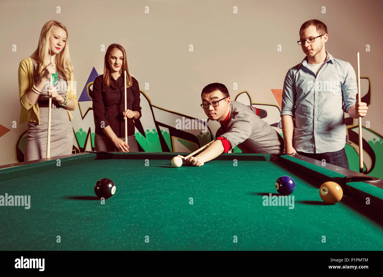 A group of young millennial business professionals playing a game of pool together on a work break; Sherwood Park, Alberta, Canada - Stock Image