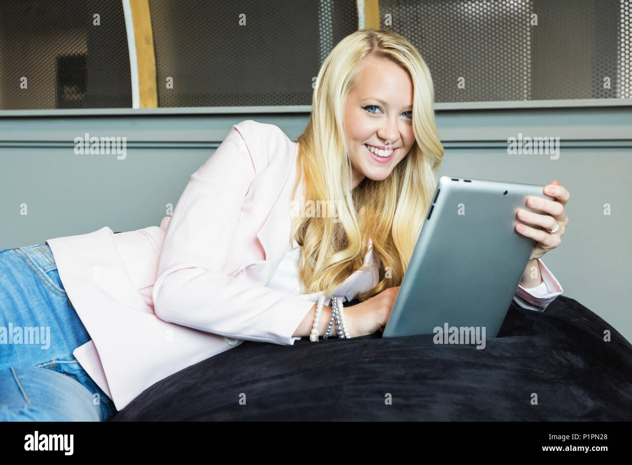 Business portrait of a beautiful young millennial businesswoman with long blond hair holding a tablet and posing for the camera in the workplace - Stock Image