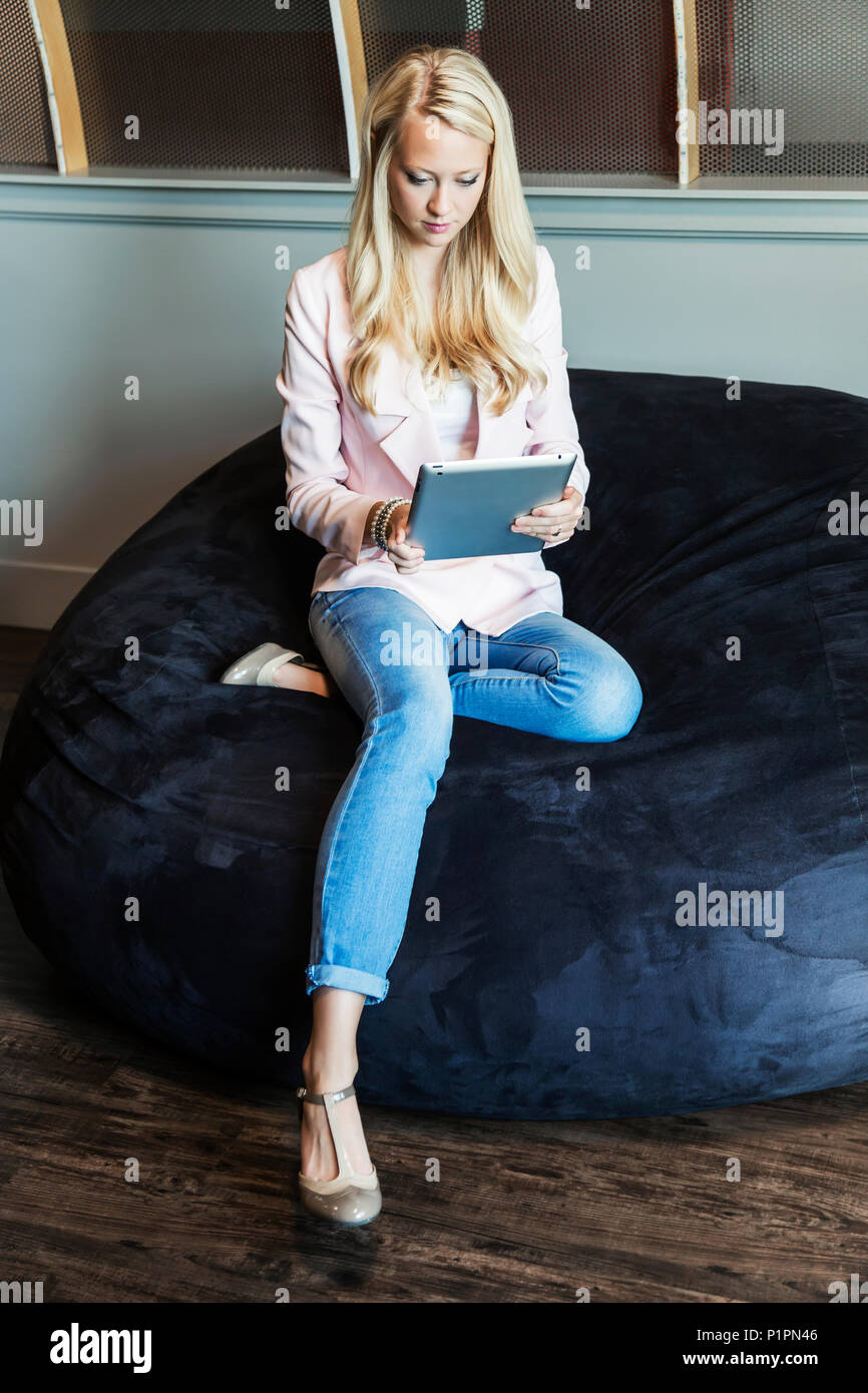 A beautiful young millennial business woman with long blond hair in the workplace using technology; Sherwood Park, Alberta, Canada - Stock Image