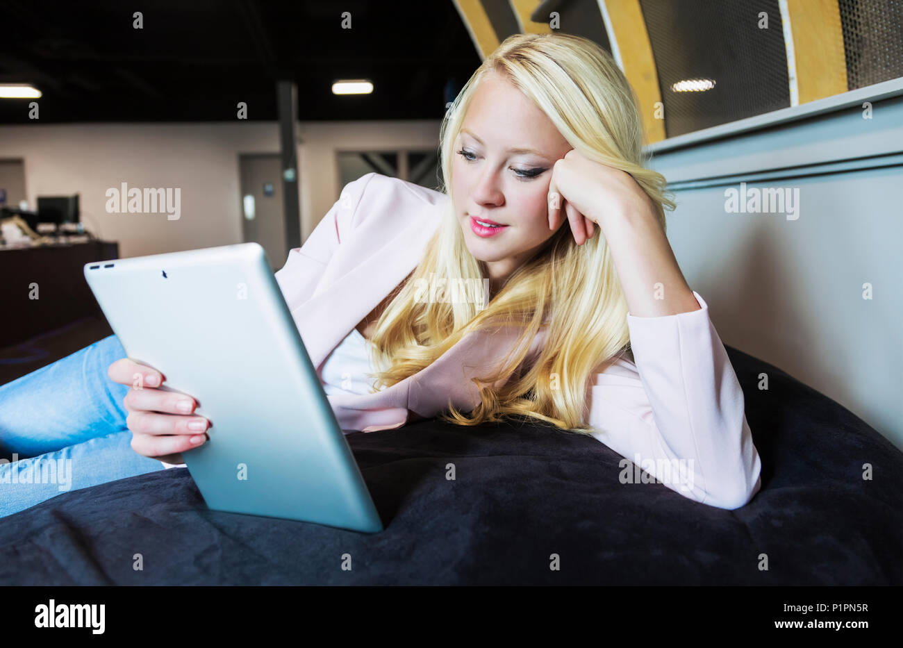 Beautiful young millennial business woman with long blond hair in the workplace on a beanbag chair using a tablet; Sherwood Park, Alberta, Canada - Stock Image