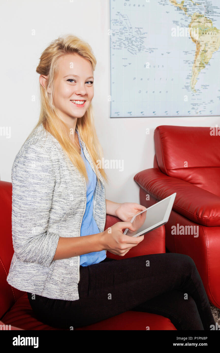 A beautiful young millennial business woman with long blond hair using her tablet in the lobby of a workplace while waiting for a job interview - Stock Image