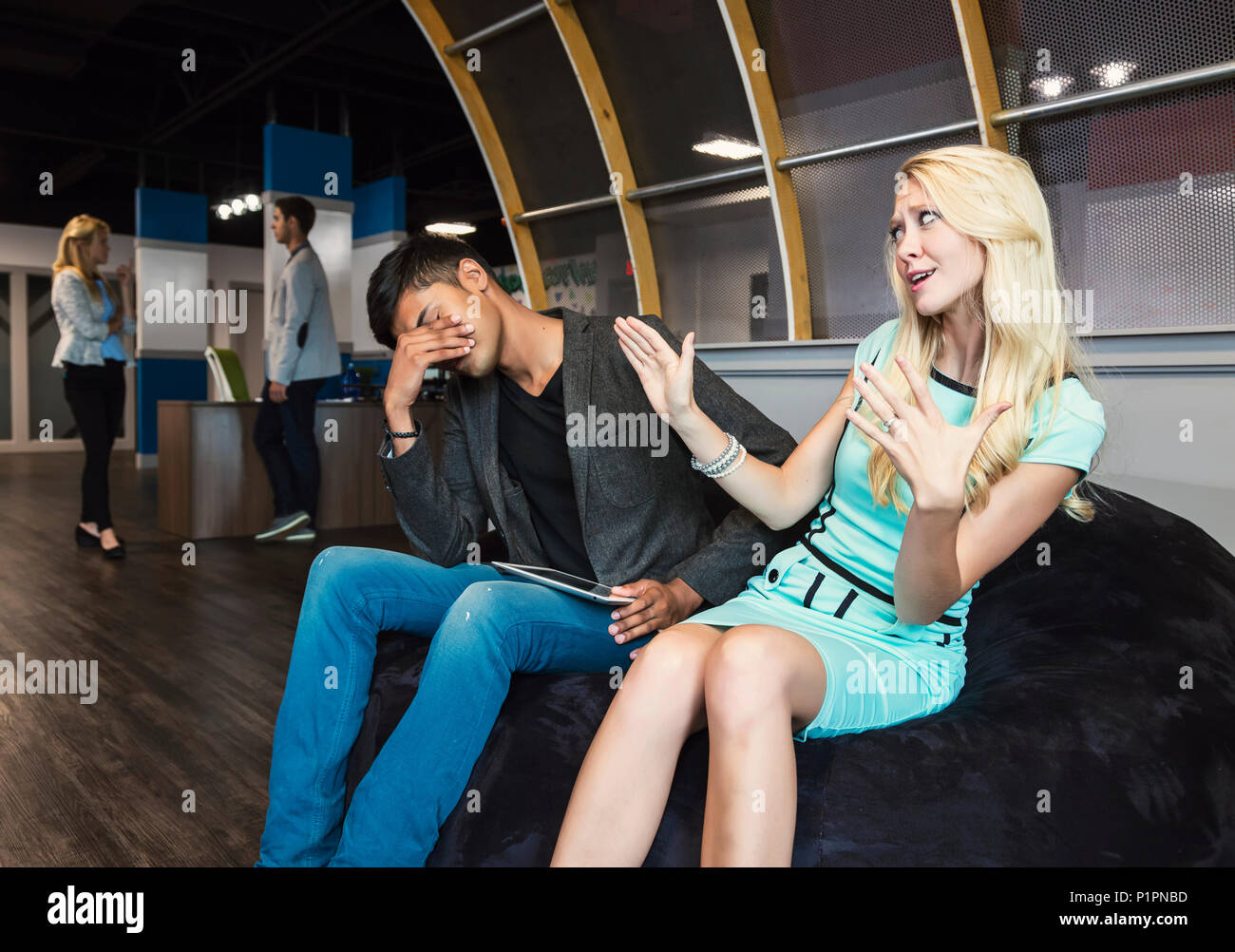 Two young millennial business professionals have a disagreement in their place of work; Sherwood Park, Alberta, Canada - Stock Image