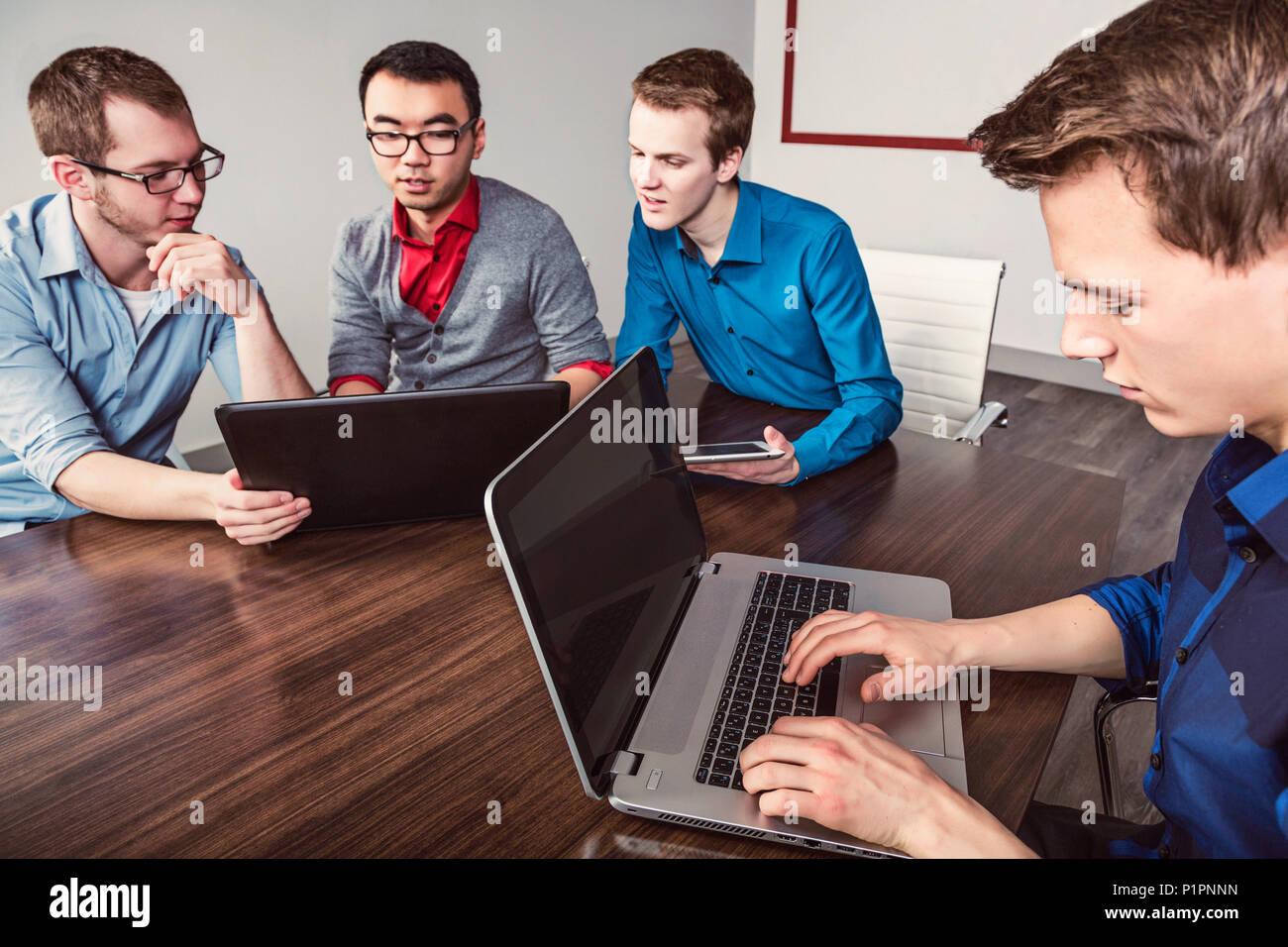 Young men who are millennial business professionals working together in a conference room in a high tech modern business - Stock Image