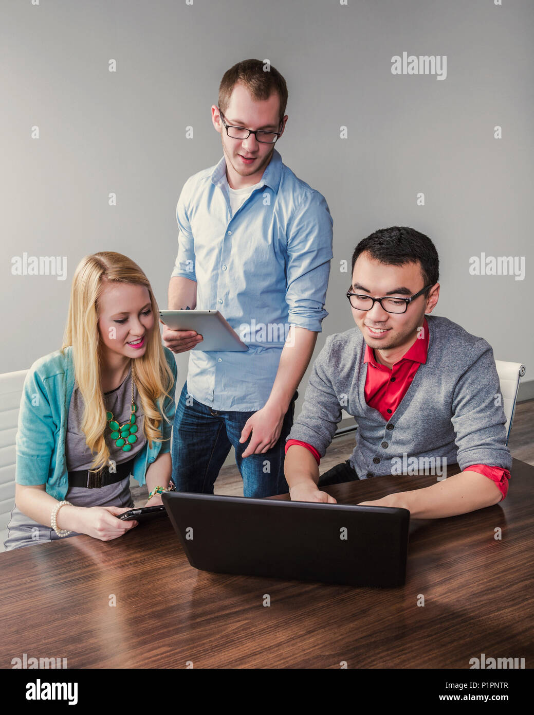 Young millennial business professionals working together in a conference room in a high tech modern business; Sherwood Park, Alberta, Canada - Stock Image