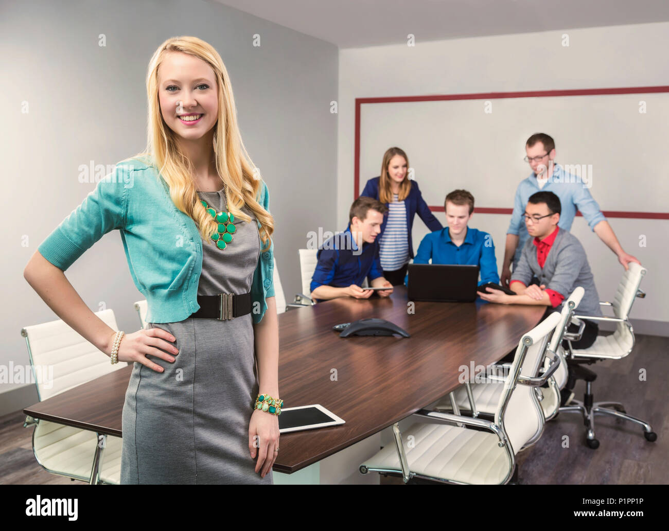 A beautiful young millennial business woman working on her tablet in a conference room with her co-workers; Sherwood Park, Alberta, Canada - Stock Image