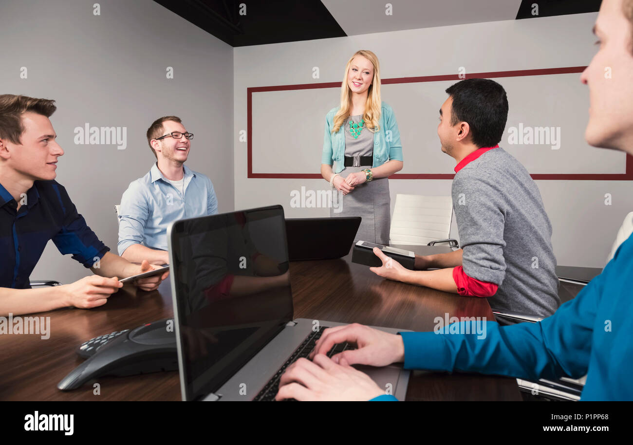 Young millennial businesswoman giving a presentation to other business professionals working in a conference room in a modern place of business - Stock Image