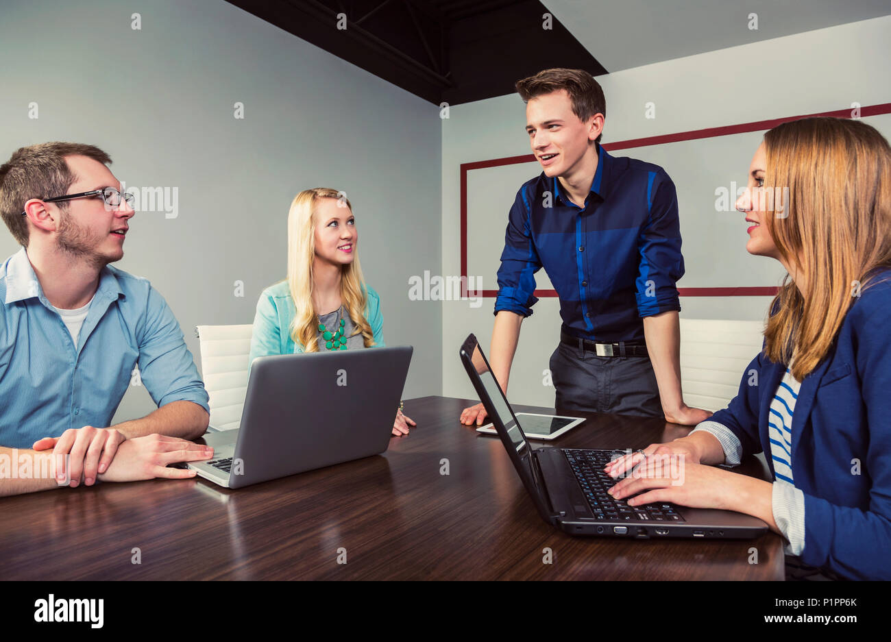 Young millennial businessman speaking to a group of young professionals in a conference room in a place of business; Sherwood Park, Alberta, Canada - Stock Image
