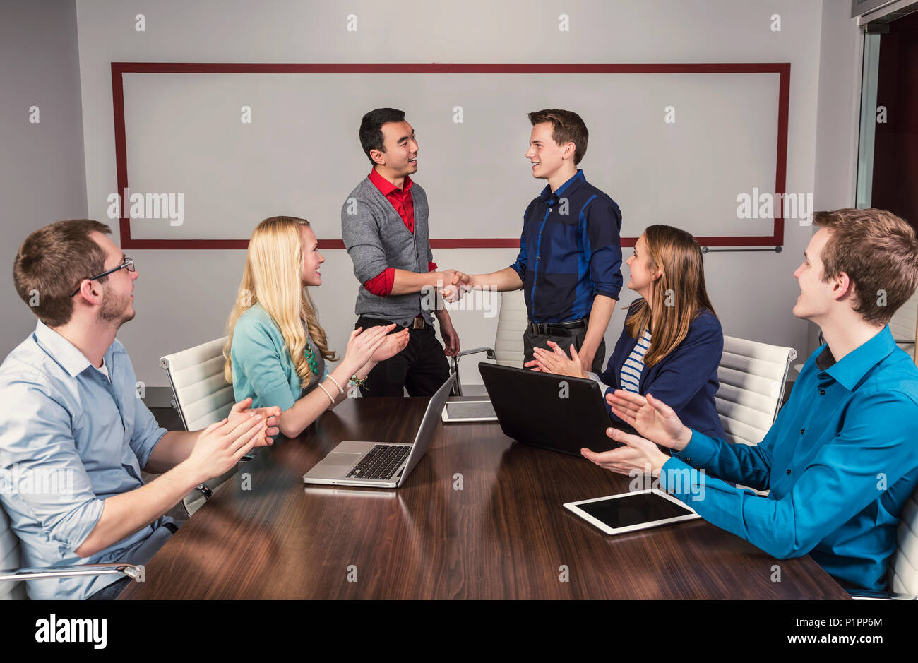 Young millennial business professionals working together in a conference room in a place of business and praising the efforts of one of their peers - Stock Image