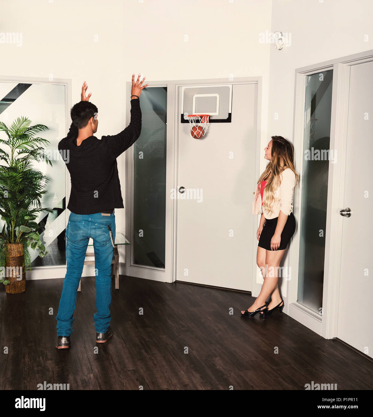 Two young millennial business co-workers taking a break in the workplace and shooting a basketball into a net; Sherwood Park, Alberta, Canada - Stock Image