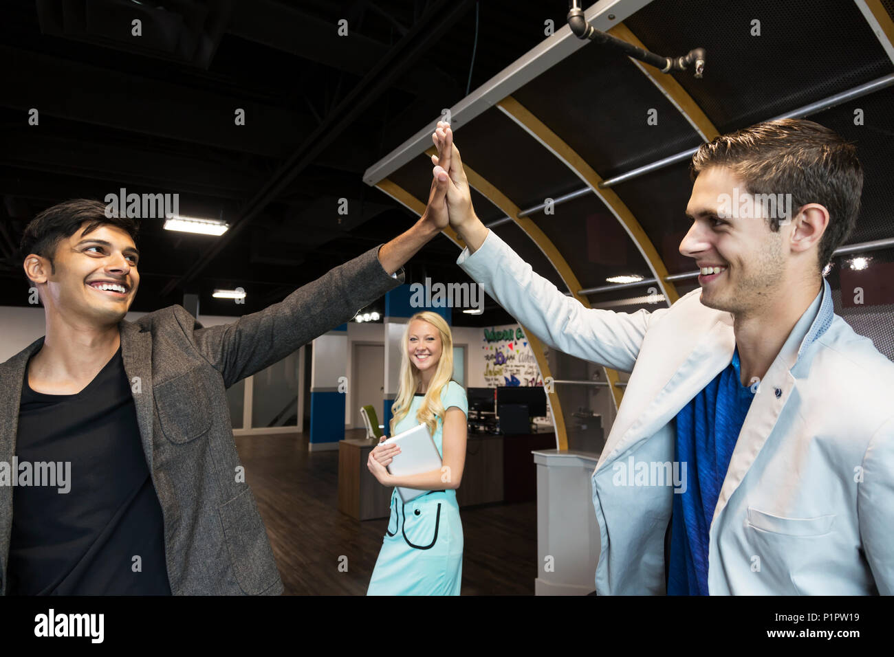 Young millennial business co-workers celebrating a success with a high-five in the workplace; Sherwood Park, Alberta, Canada - Stock Image
