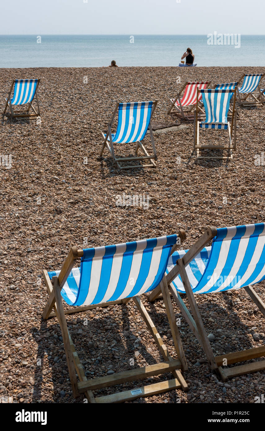 stripey deckchairs on the beach at Brighton, East Sussex, UK - Stock Image