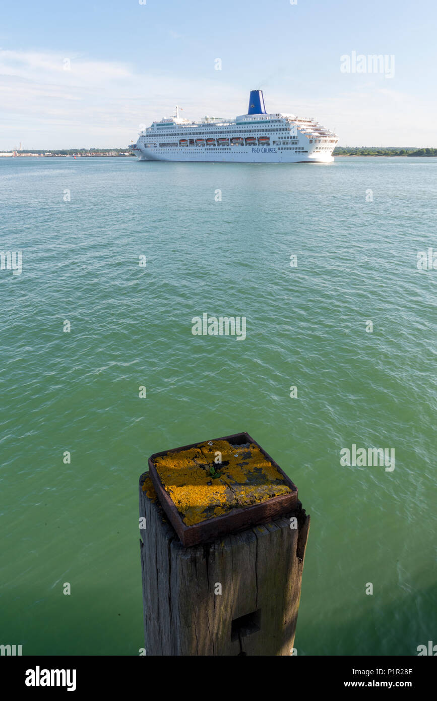 the p and o cruise liner oriana leaving the port of southampton on a cruise in warmer waters with an old wooden post in foreground to give perspective - Stock Image