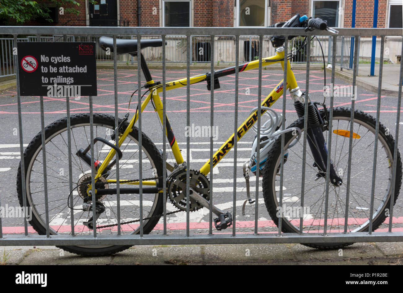 no cycles to be chained to these railings funny. a bicycle clearly flouting the law and making a mockery of the sign prohibiting parking of bicycles. - Stock Image