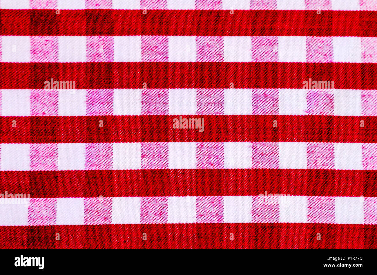 Red and white checked or striped gingham tablecloth, for use as a background or wallpaper - Stock Image