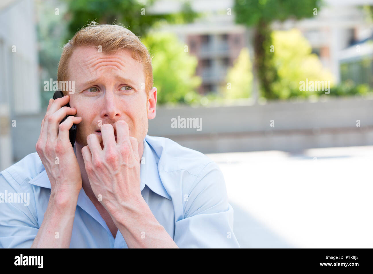 Closeup portrait, worried young man in blue shirt talking on phone to someone, looking gloomy, isolated outdoors outside background - Stock Image