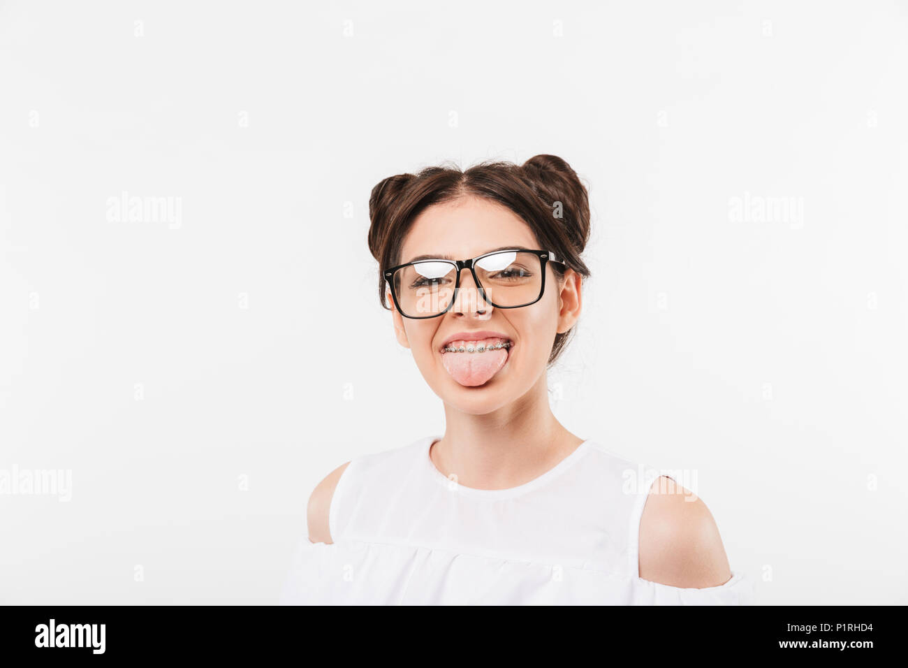 Portrait of a cheerful young girl in sunglasses sticking her tongue out isolated over white background - Stock Image