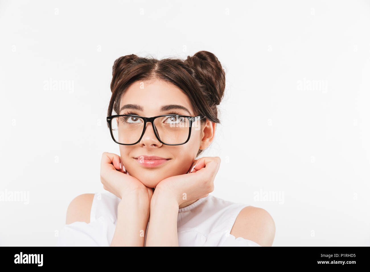 Portrait of a smiling young girl in sunglasses looking up at copy space isolated over white background - Stock Image