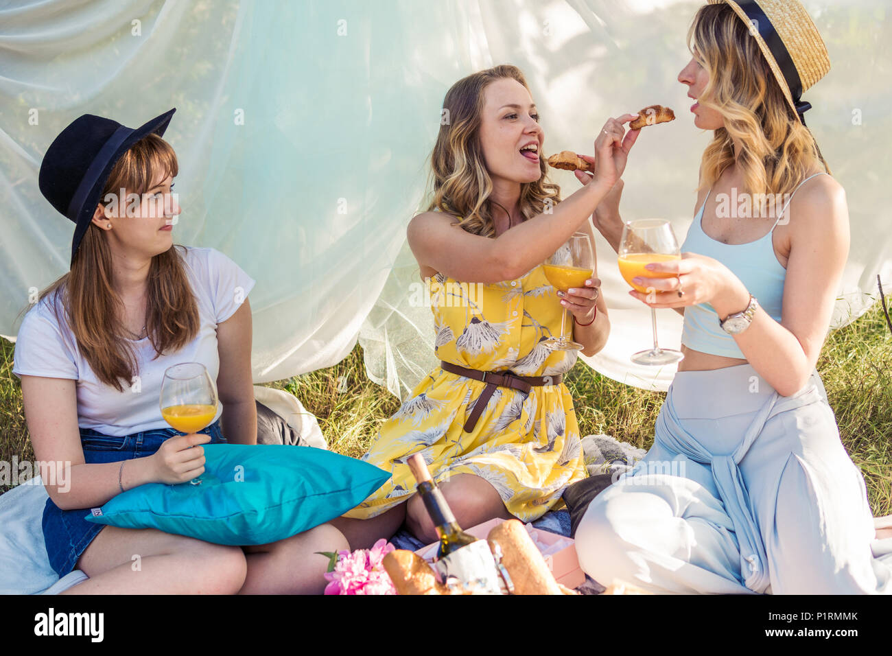 Group of girls friends making picnic outdoor. They feed each other with a croissant - Stock Image