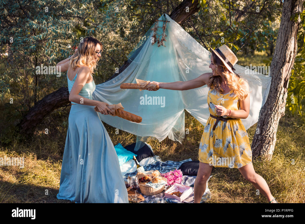Playful girls fighting with bread baguette making picnic outdoor. bachelorette, party - Stock Image