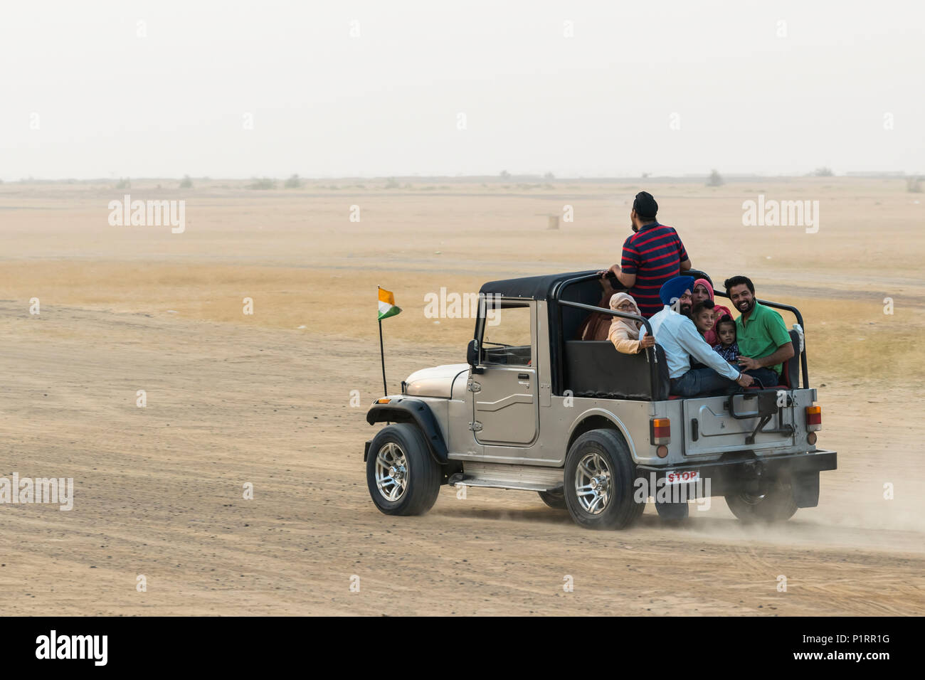 A family rides in the back of a recreational vehicle exploring the Sam sand dunes; Damodara, Rajasthan, India - Stock Image