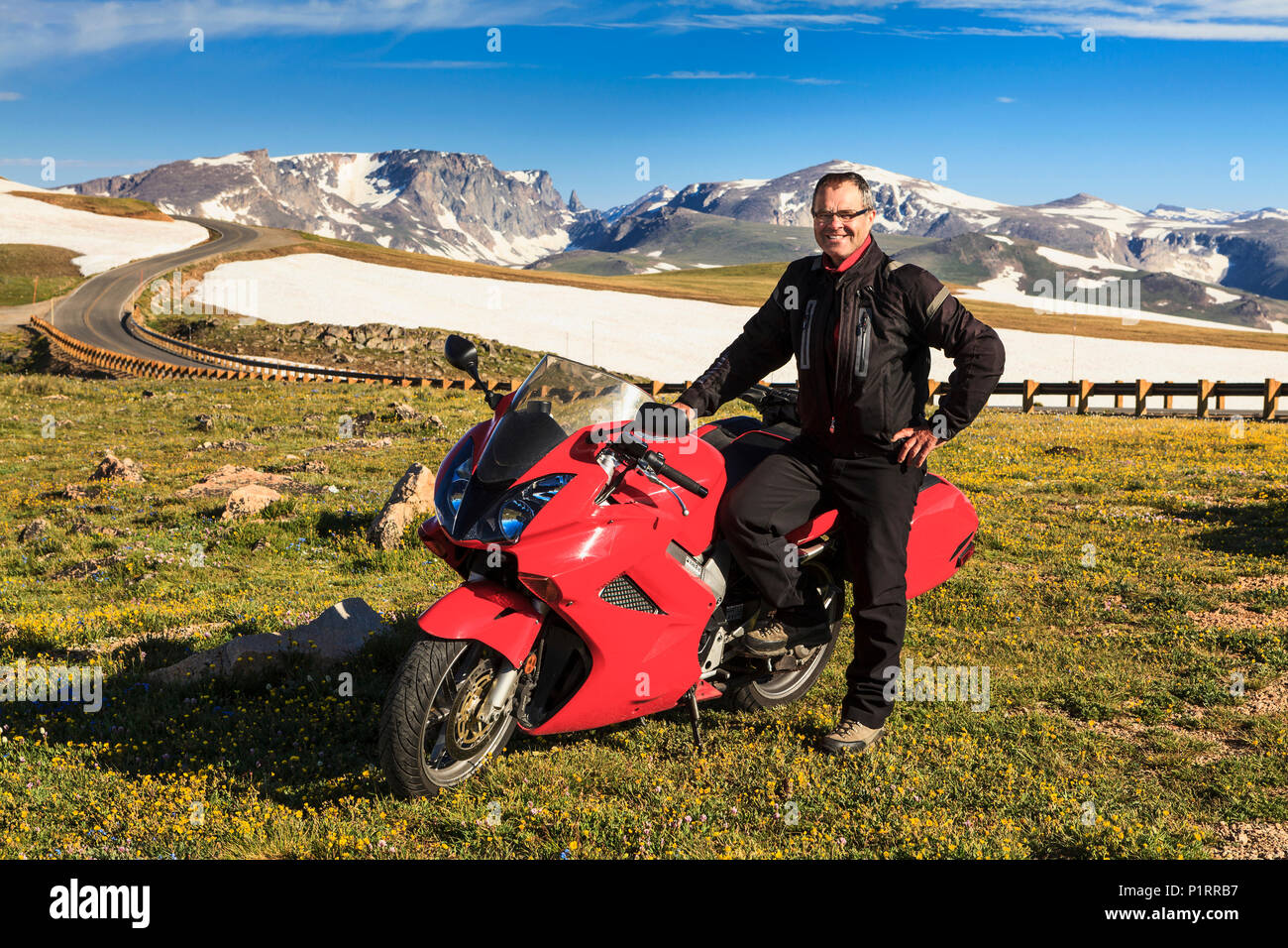 View from the Beartooth Highway of the Beartooth Mountains and a man posing with a motorcycle parked on the roadside Stock Photo