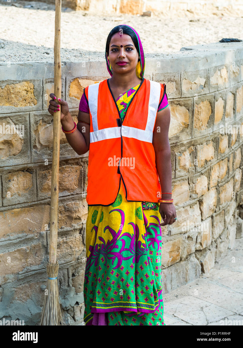 Portrait of an Indian woman wearing a reflective vest and holding a broom; Jaisalmer, Rajasthan, India - Stock Image