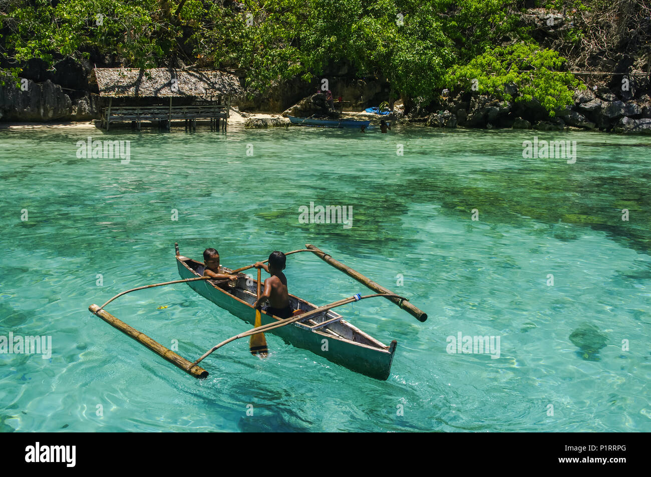 Boys paddling in an outrigger canoe, fishing in the turquoise waters of the Indian Ocean; Andaman Islands, India - Stock Image