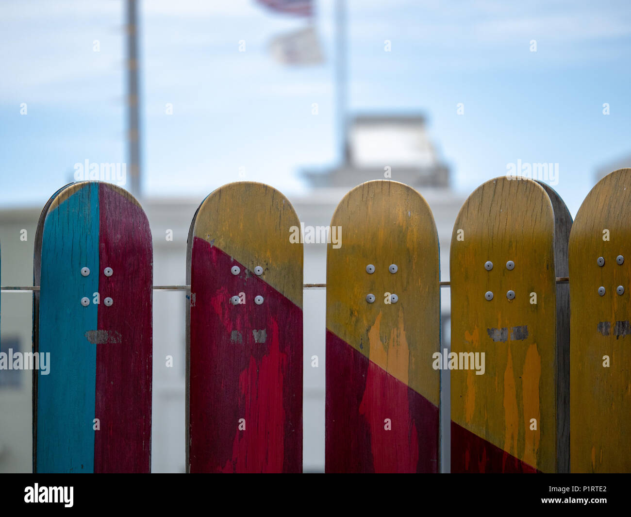 2e063eb2 A number of teal, red, yellow weathered skateboards mounted on railing -  Stock Image