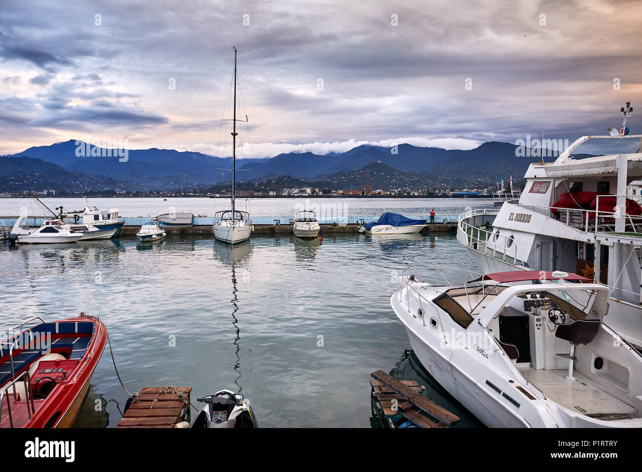 BATUMI, GEORGIA – OCTOBER 3, 2017: Sea Port with fishing boats and yacht at overcast stormy sky - Stock Image