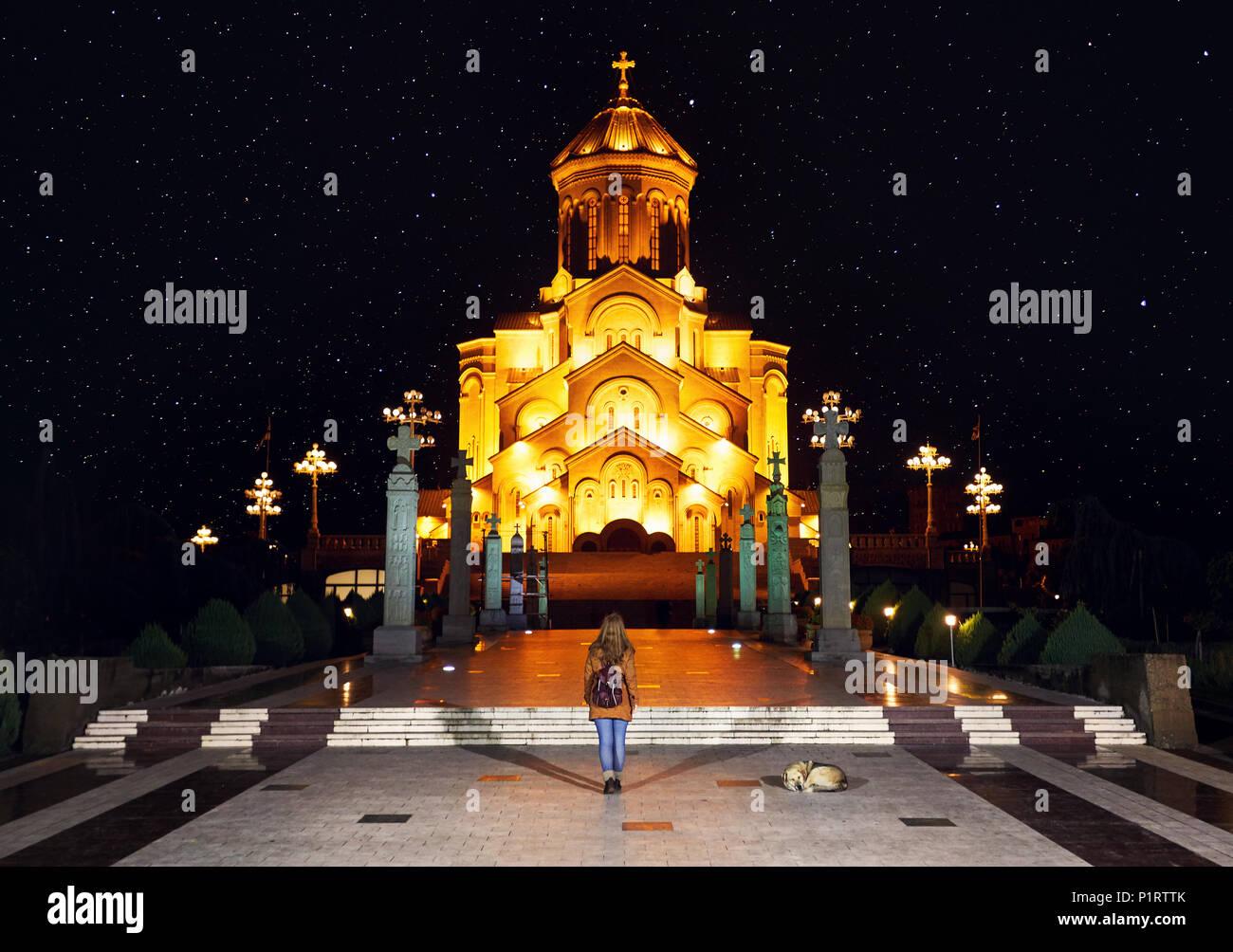 Woman near The Holy Trinity Cathedral or Tsminda Sameba Church at night in Tbilisi, Georgia Stock Photo