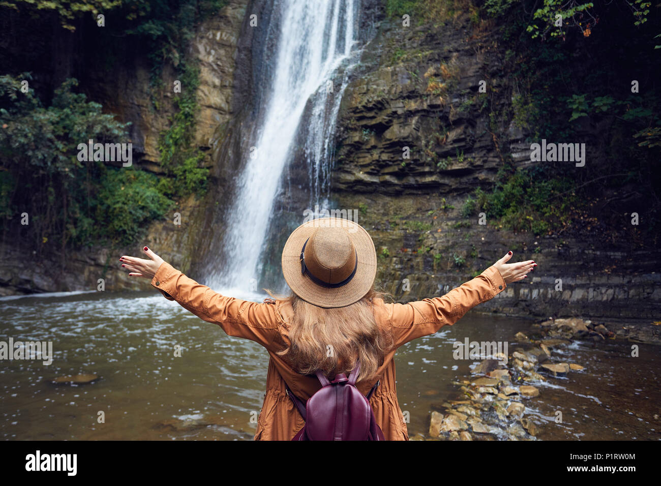 Woman in Hat rise her hand near waterfall in Botanical Garden in Tbilisi, Georgia - Stock Image