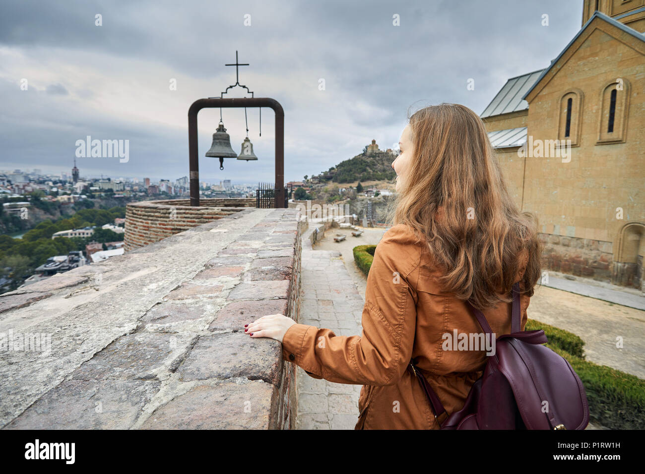 Tourist woman near Bells at Cathedral in Old medieval castle Narikala at overcast cloudy sky in Tbilisi, Georgia - Stock Image