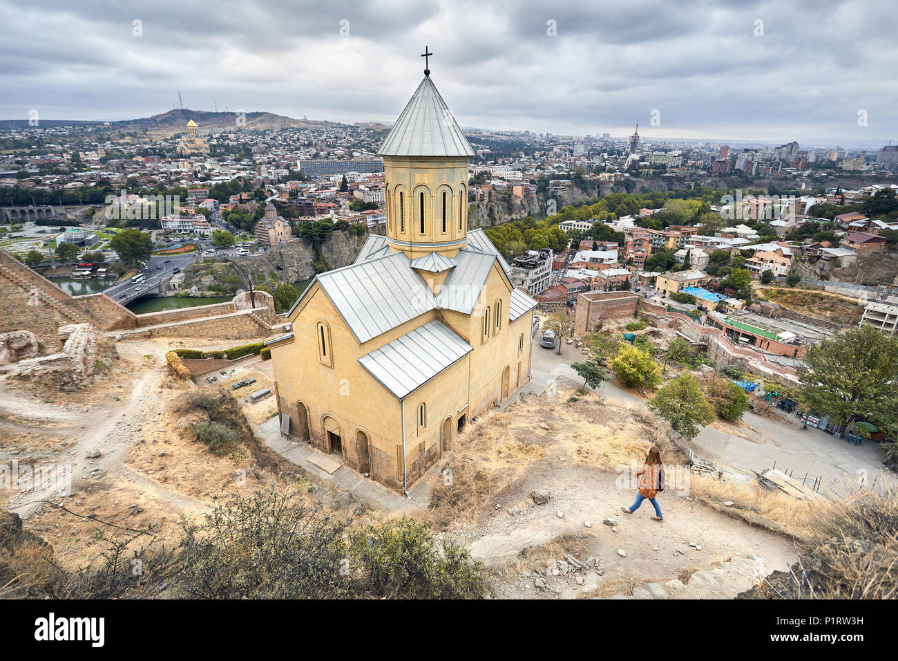 Tourist woman walking near Cathedral in Old medieval castle Narikala at overcast cloudy sky in Tbilisi, Georgia - Stock Image