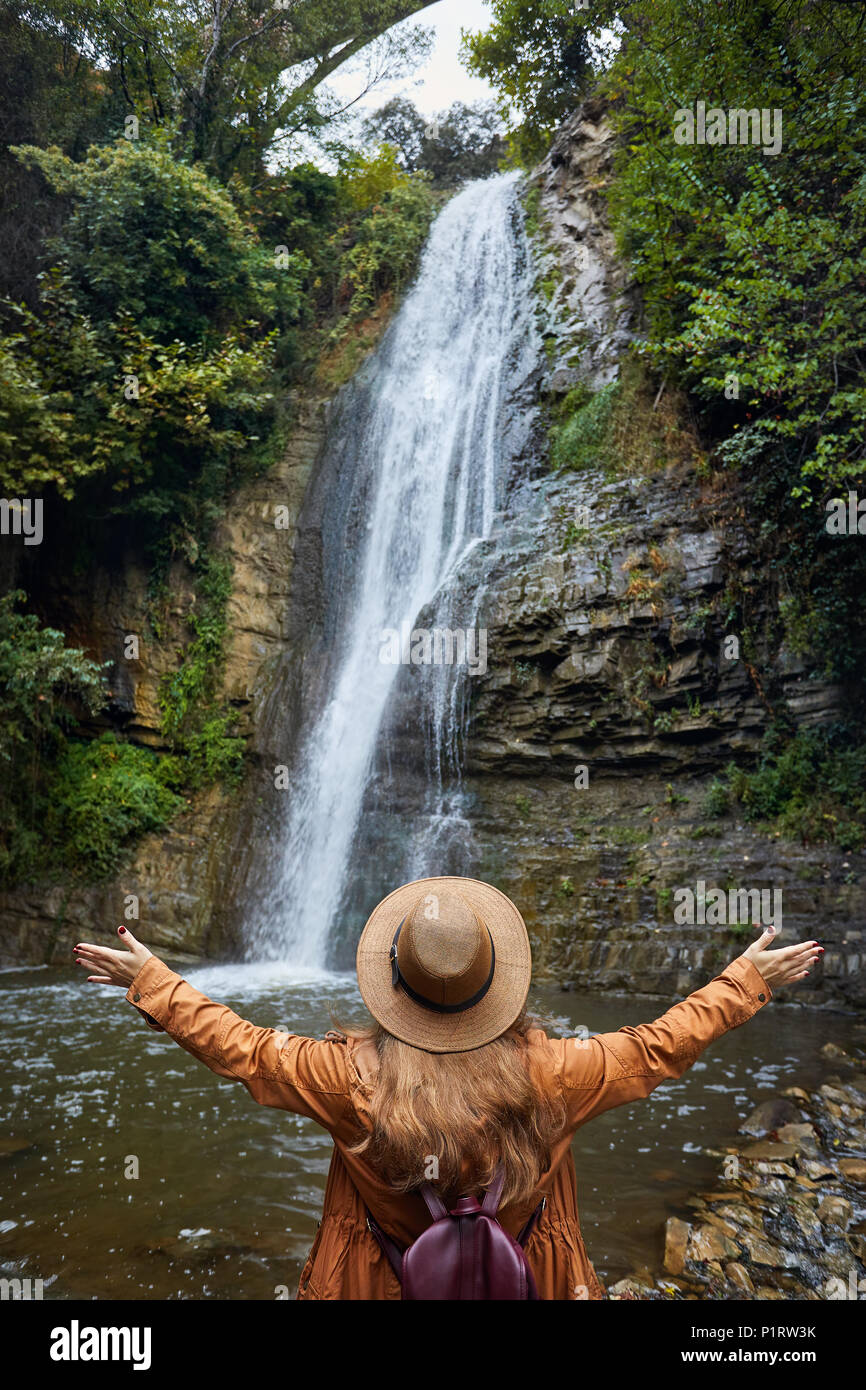 Woman in Hat rise her hand near waterfall in Botanical Garden in Tbilisi, Georgia - Stock Image
