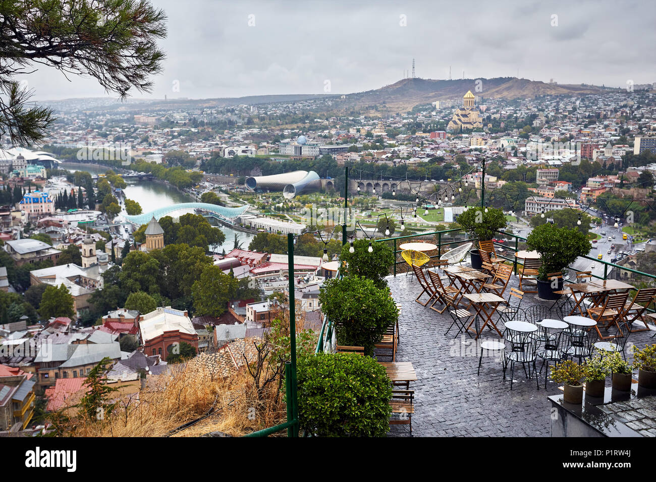 Empty cafe at Narikala Fortress with panoramic view Tbilisi at overcast sky, Georgia - Stock Image