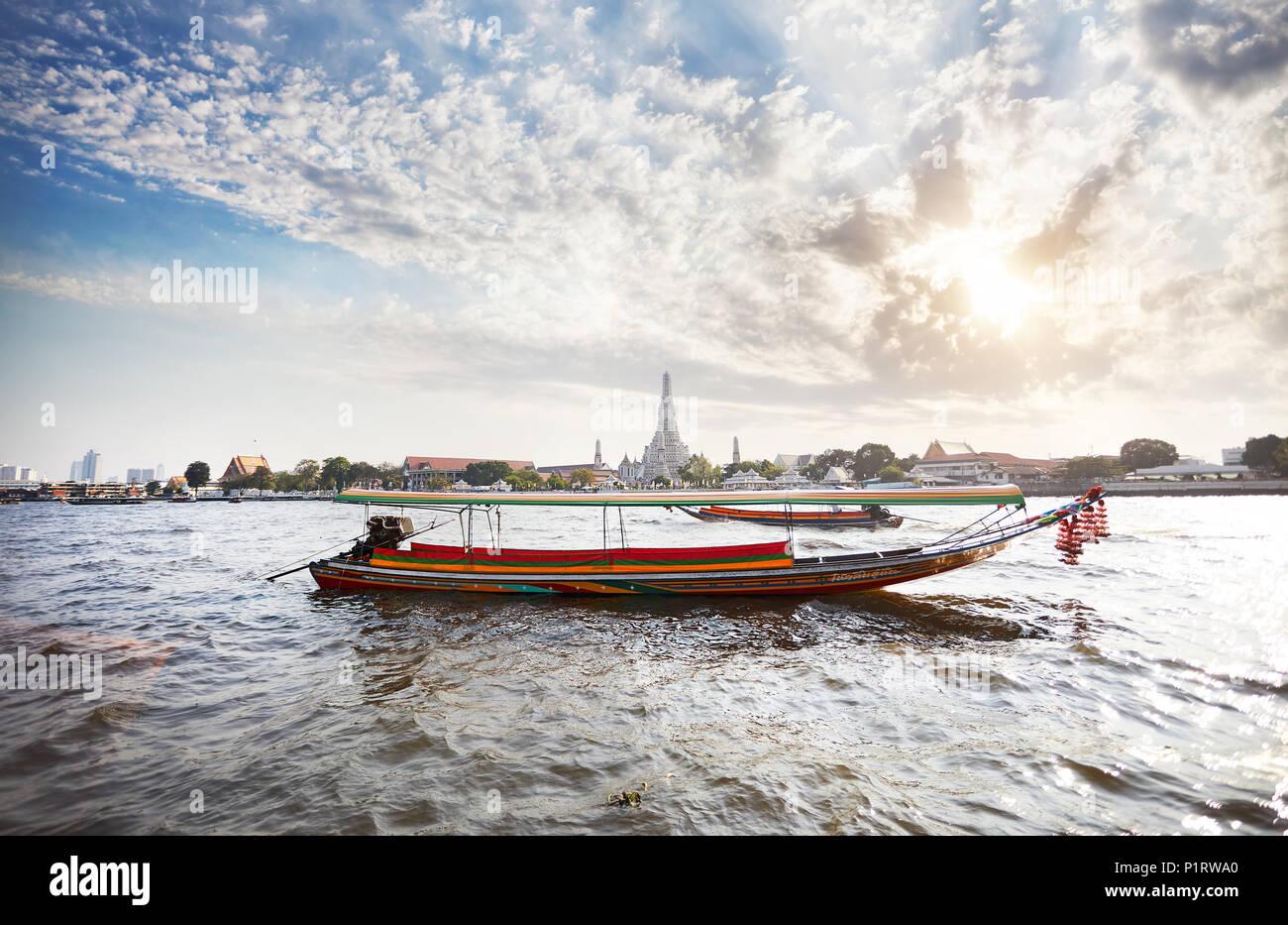 Traditional Thai Long tail boat in Chao Phraya river near Wat Arun at sunset in Bangkok, Thailand - Stock Image