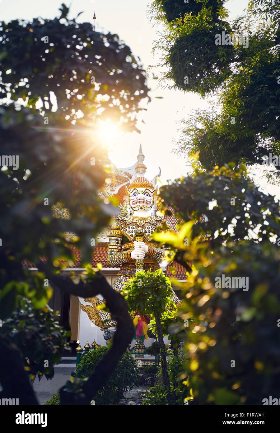 Giant Demon stature near Buddhist temple Wat Arun in Bangkok at Sunset - Stock Image