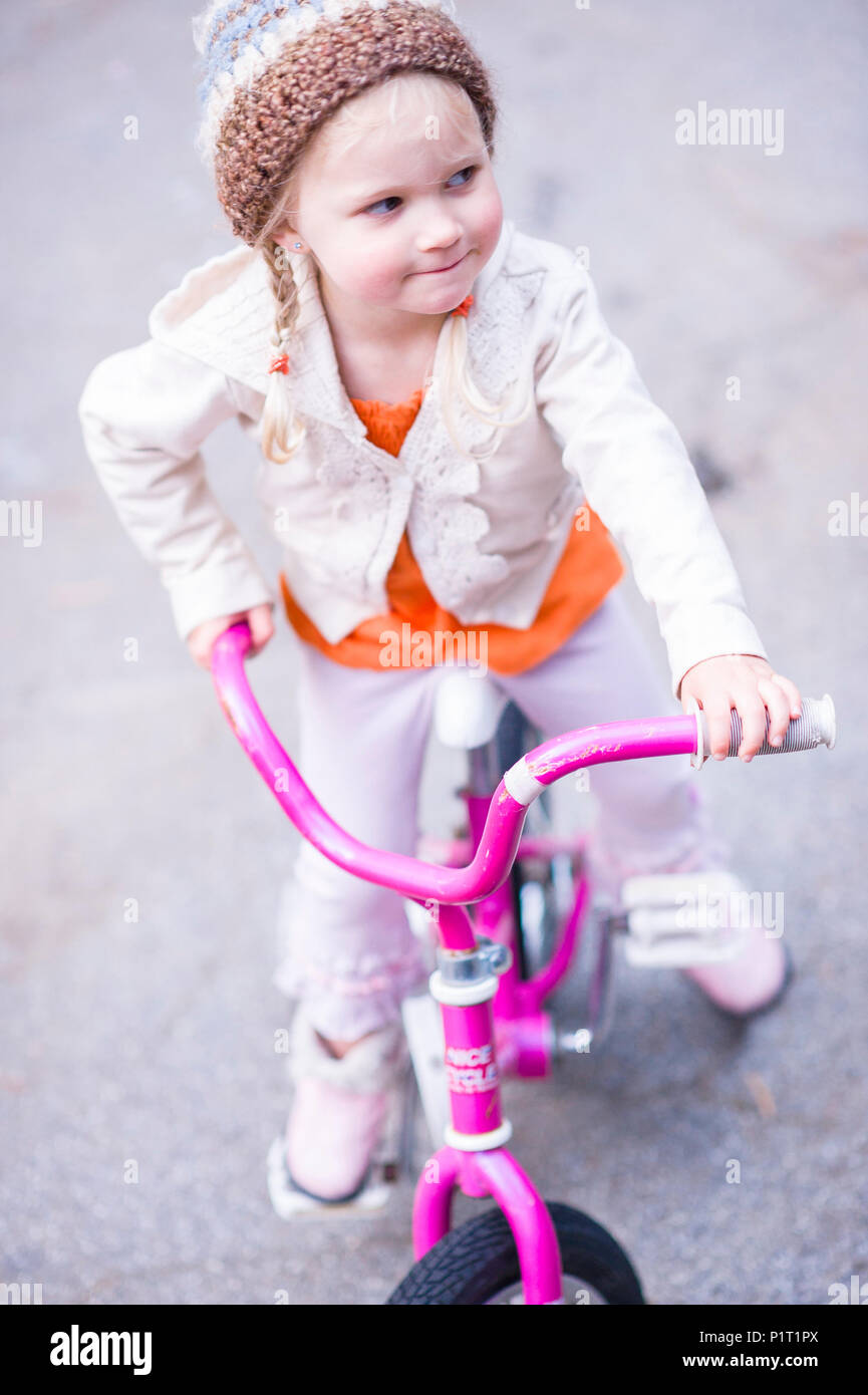 Young girl in stylish clothing on her pink bicycle Stock Photo
