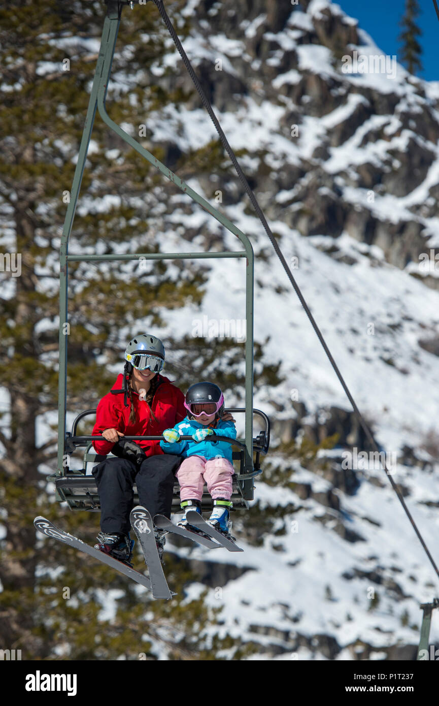Mother and young daughter on a ski lift at Squaw Valley Ski Resort in California, North America. - Stock Image