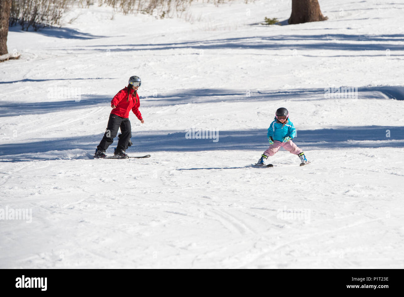 Mother teaching young daughter how to ski at Squaw Valley Ski Resort in California, North America. - Stock Image
