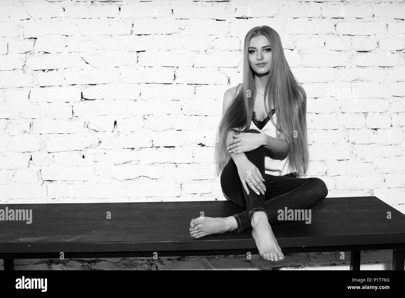 Young beautiful woman with long straight blonde hair in blue jeans and bright blouse sitting on black wooden table with crossed legs and looking in ca - Stock Image
