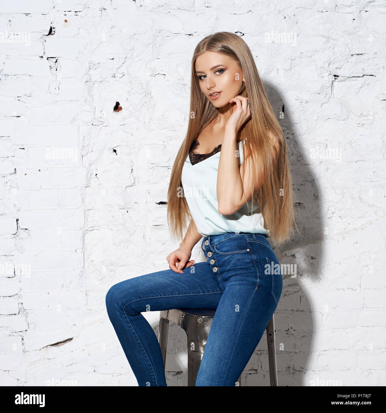 Young beautiful woman with long straight blonde hair in blue jeans and bright blouse sitting on white high bar chair with crossed legs and looking in  - Stock Image