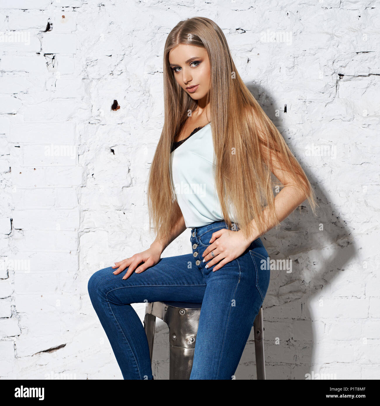 Young Woman In White Sweater And Jeans Sitting Crosslegged