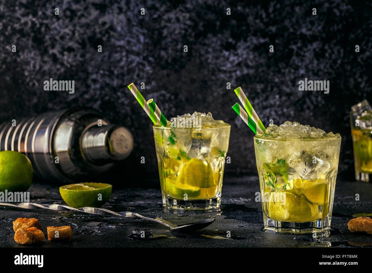 Fresh lime cocktail with ice on dark background. - Stock Image